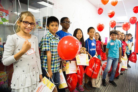 Kids showing off their balloons and Mathnasium goody bags