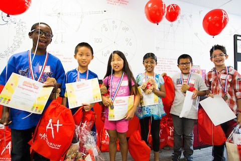 Kids holding Mathnasium balloons and goodies
