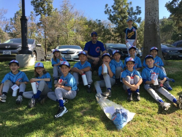 Local little league team smiling together on the grass