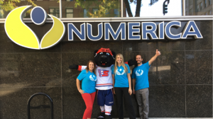Group of Numerica employees in blue CIC shirts outside of the Downtown Numerica branch posing with Spokane Chiefs Mascot
