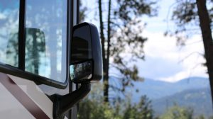 Close shot of an RV's right side with a mirror and half of the side window overlooking pine trees and mountains.