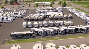 Aerial view of Blue Dog RV. Multiple RVs in a parking lot facing different directions with grass and trees in the background.
