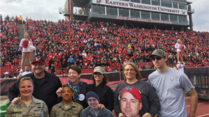 Five people are posing for a picture in front of football stands and cheerleaders holding different cut outs of people at an Eastern Washington University football game.