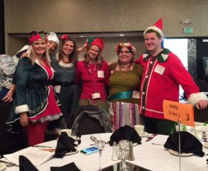 Five employees pose for a picture at a dinner party dressed up like elfs with brightly colored red costumes and unique hats.