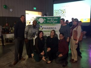 """Seven people posed for a picture in front of a sign that says """"Taking a Bite out of Hunger"""" there is a power point screen up in the background."""