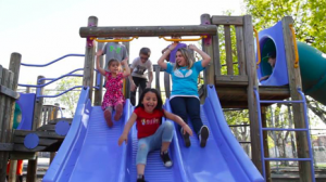 One Numerica employee wearing a blue volunteer shirt is seen playing with five kids down a slide at a playground