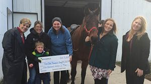 Group of Numerica employees holding a big check with a horse in the photo