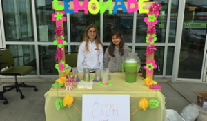 Children at a lemonade stand in front of Numerica branch