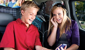 Two teens listening to music together sharing earbuds