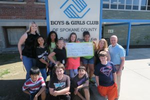 Numerica Employees and children posing with large check in front of boys and girls club