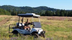 Woman on a golf cart in a field drinking a beverage