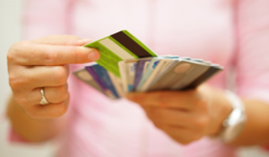 Picture of woman's hands holding several credit cards