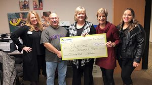 Five people standing and holding a Numerica donation check