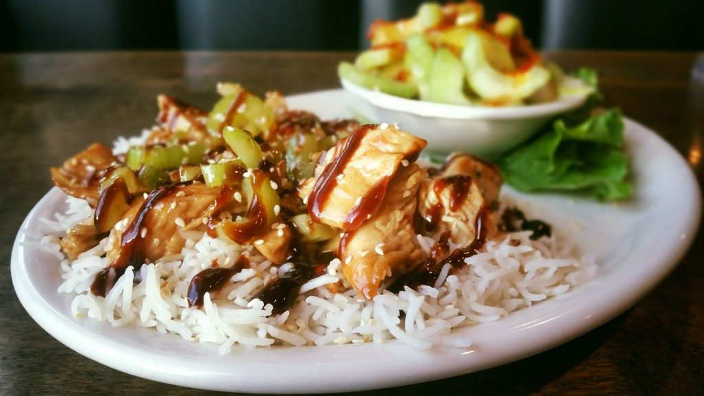 Grilled chicken drizzled with balsamic sauce over rice with cucumber salad in the background