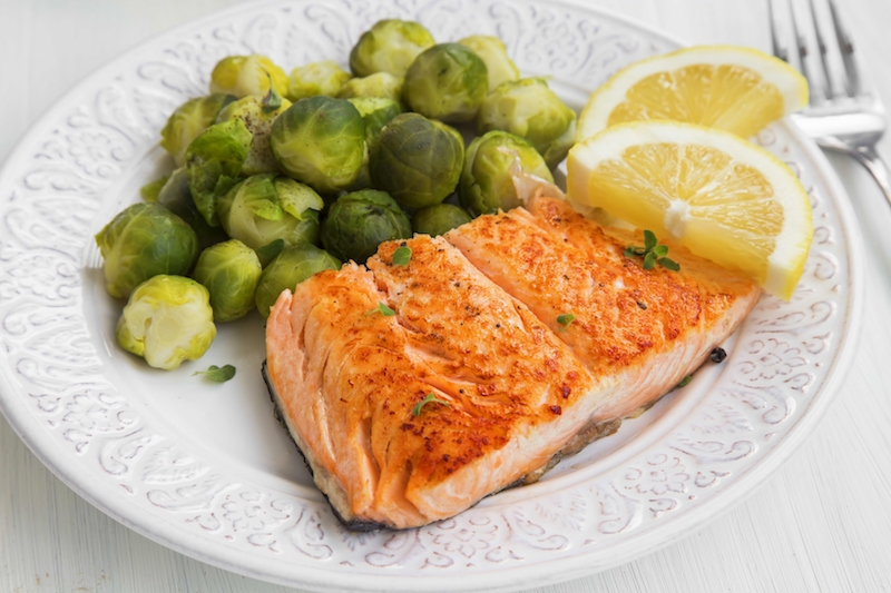 Grilled Salmon With Brussels Sprouts Garnish And Lemon Slices