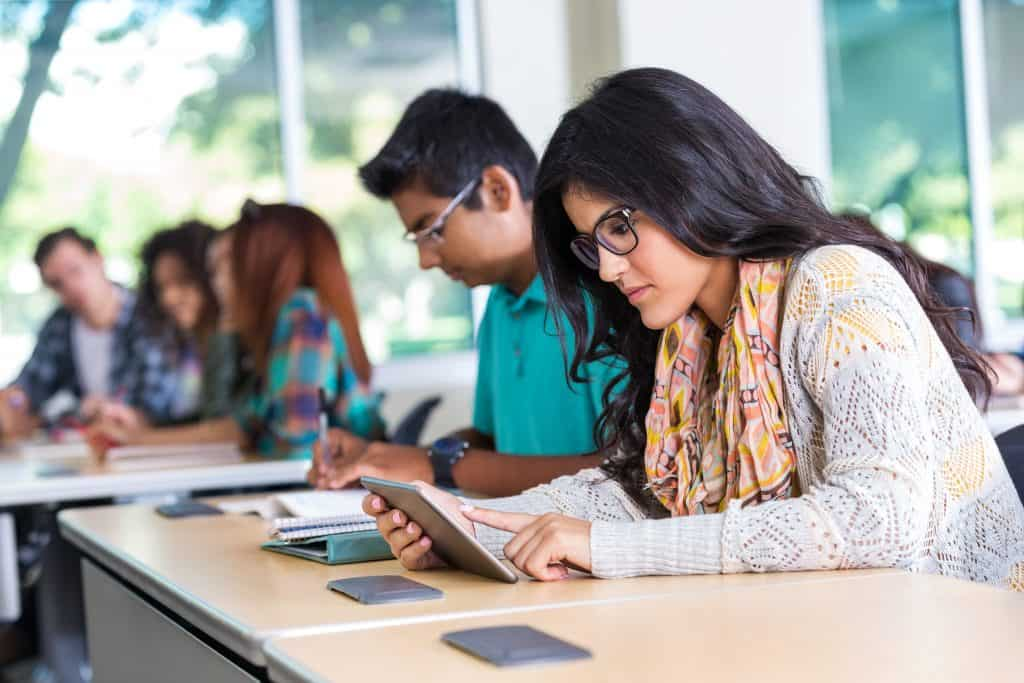 Hispanic teen using digital tablet during classroom in school
