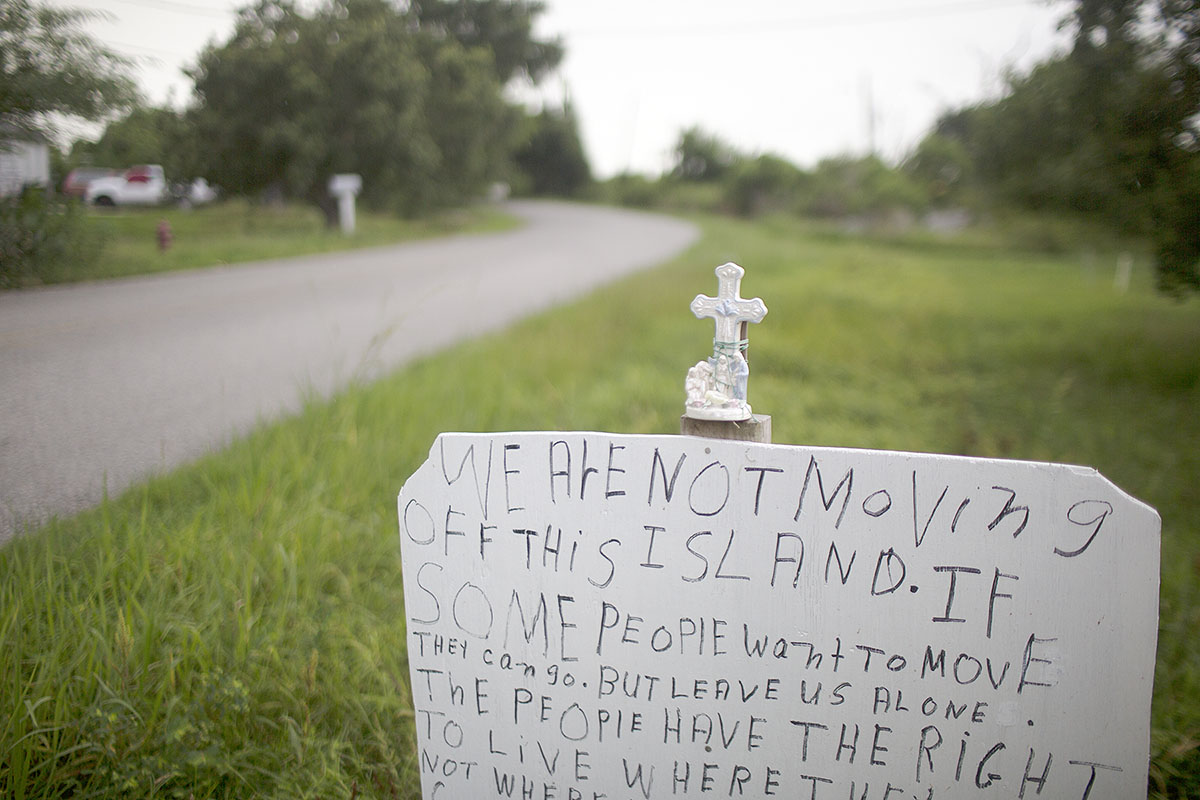 Edison Dardar attached two handwritten signs conveying his sentiments on the opposite side of the road from his home Island Road.