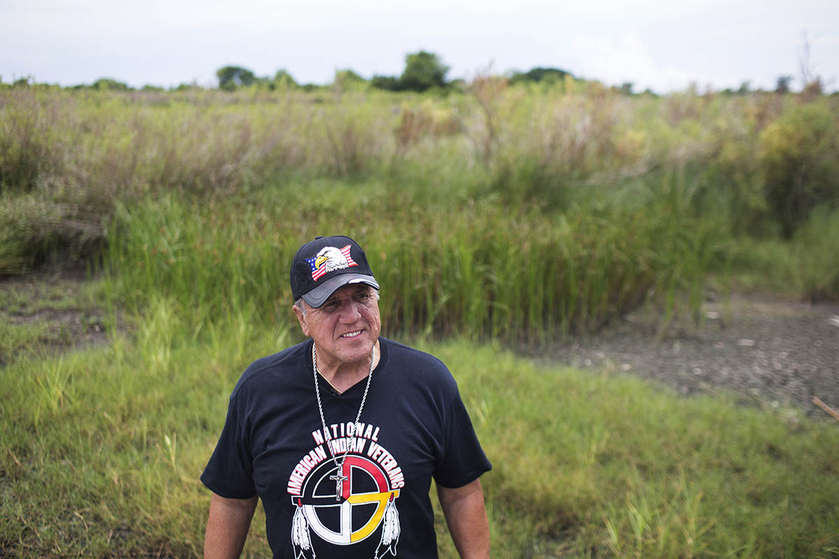Chief Albert Naquin of the Biloxi-Chitimacha-Choctaw, stands in front of the land where his childhood home once stood on Isle De Jean Charles.