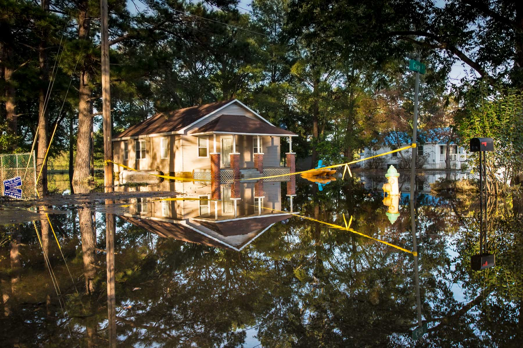 Floodwaters reflect the homes and surrounding trees of homes. (Julie Dermansky)