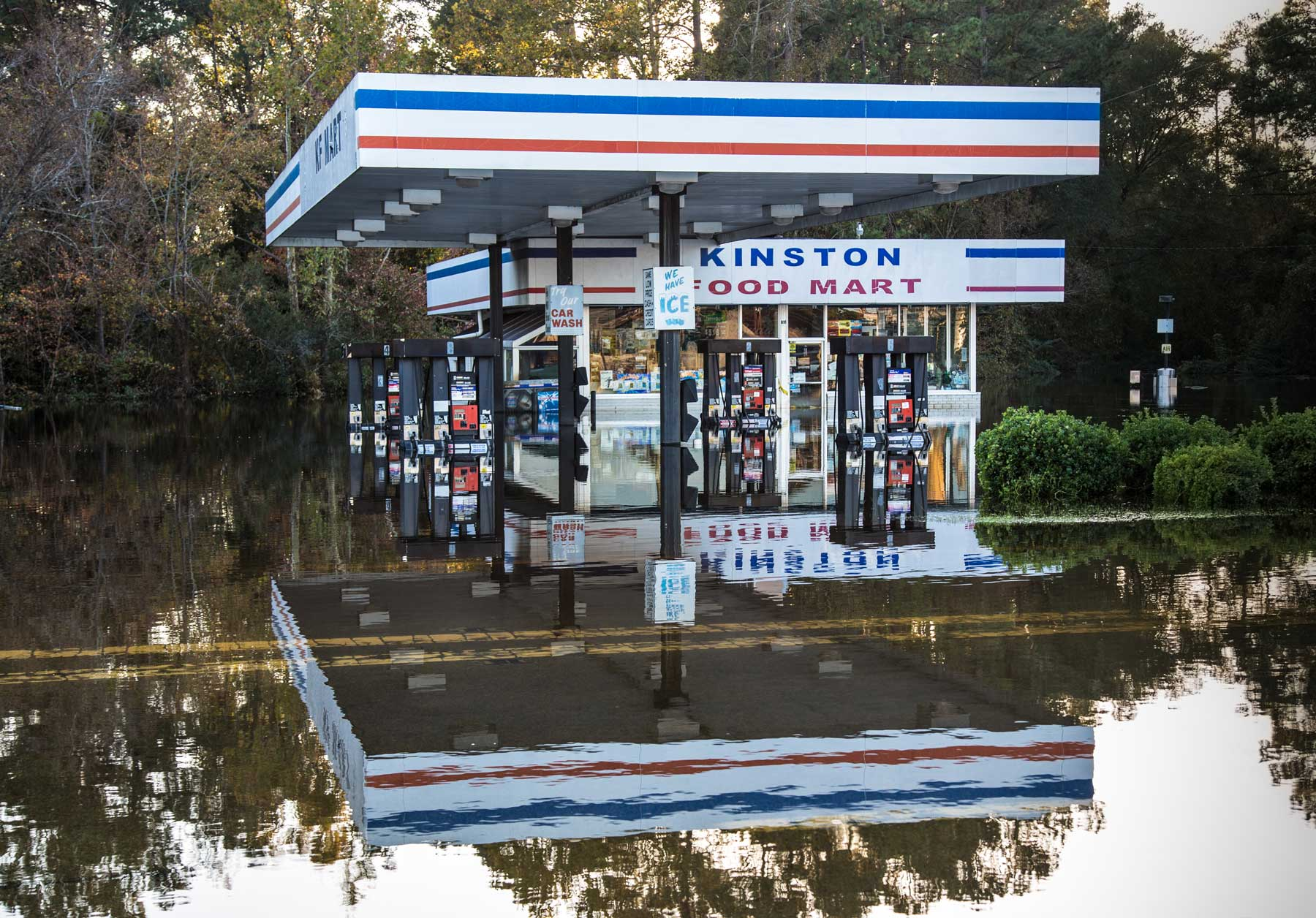 An empty gas station is clearly reflected on still floodwaters. (Julie Dermansky)