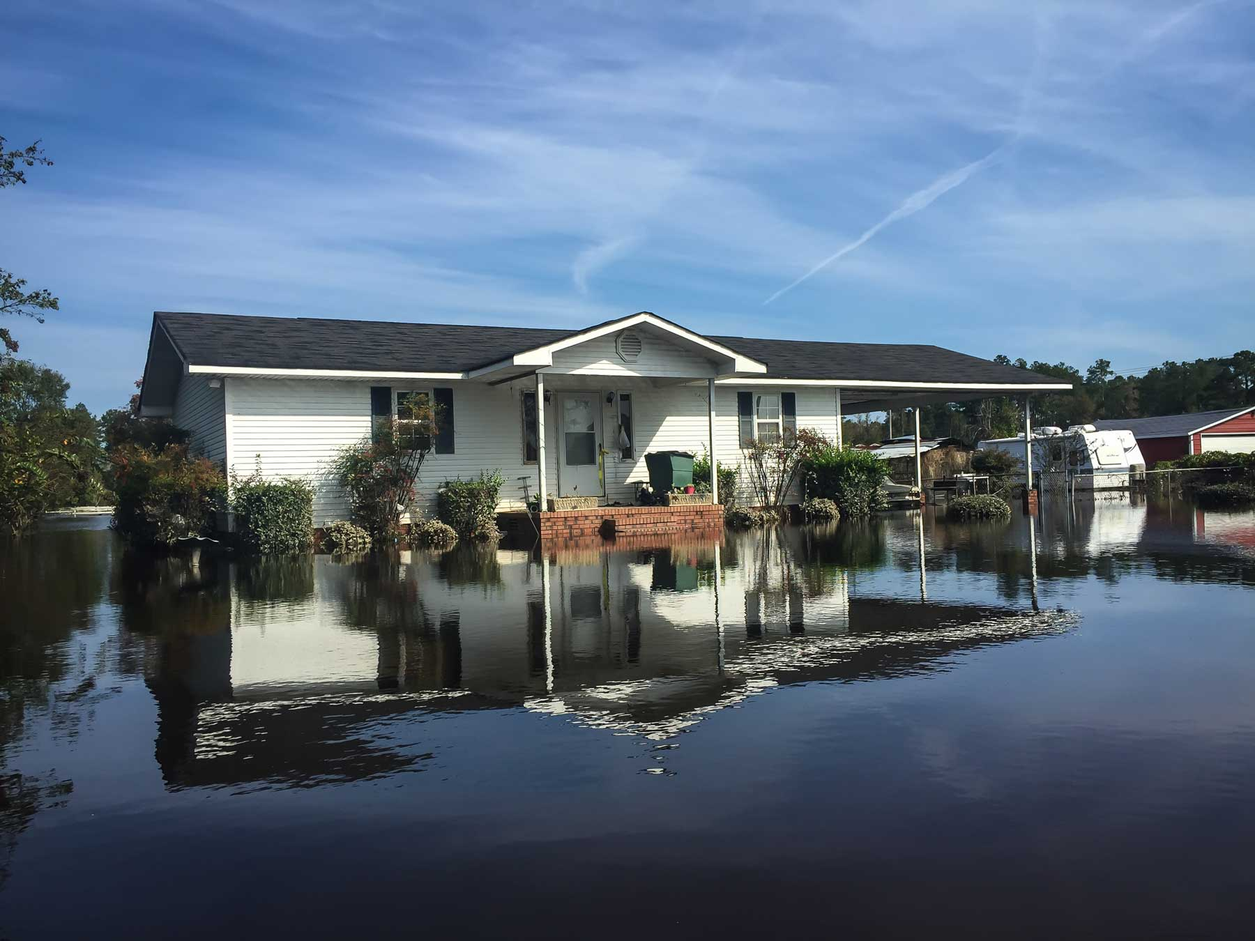 Blue skies are reflected in the floodwaters of Hurricane Matthew in Lumberton, N.C. (Julie Dermansky)