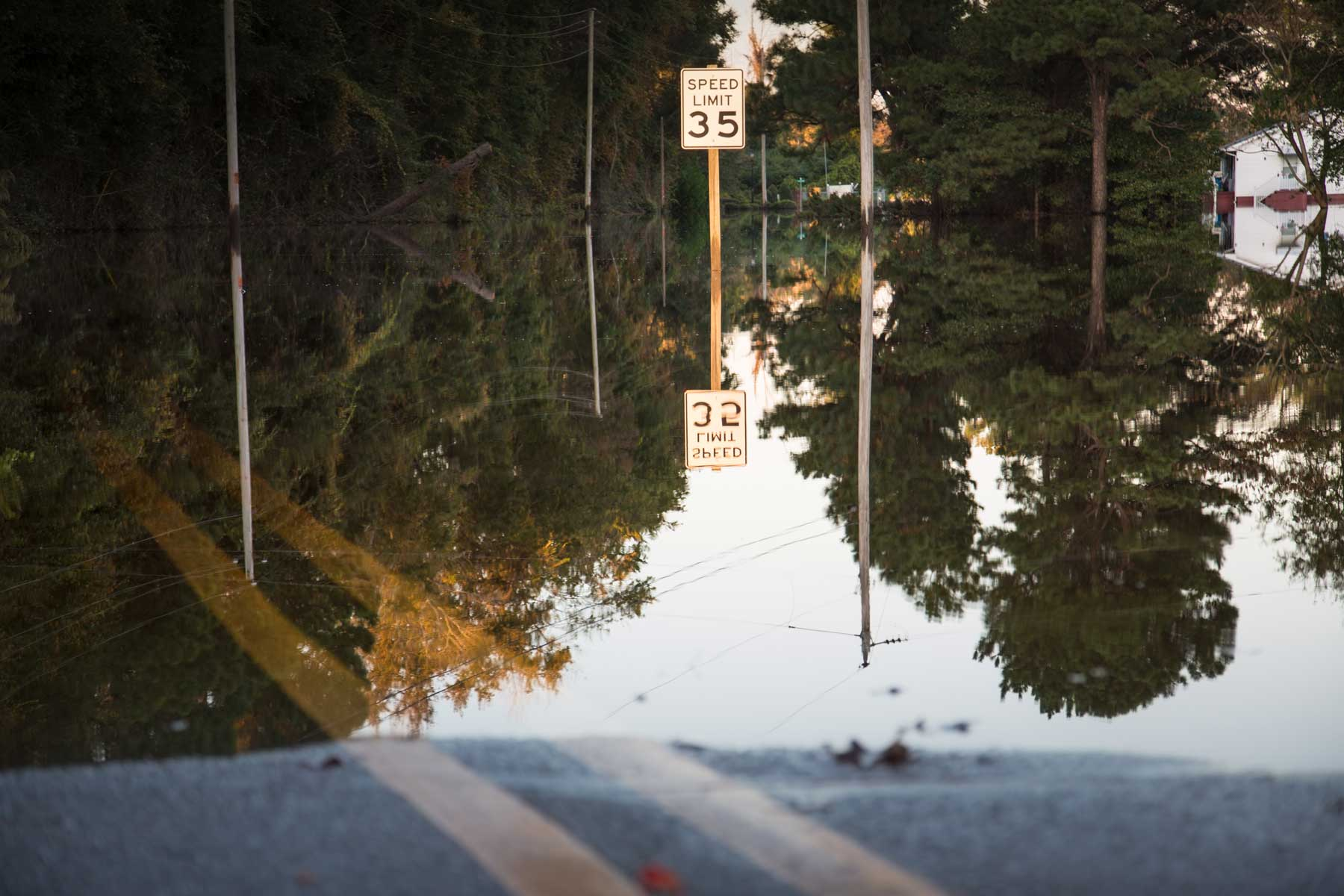 A speed limit sign is reflected over a flooded road in Kinston, N.C. (Julie Dermansky)