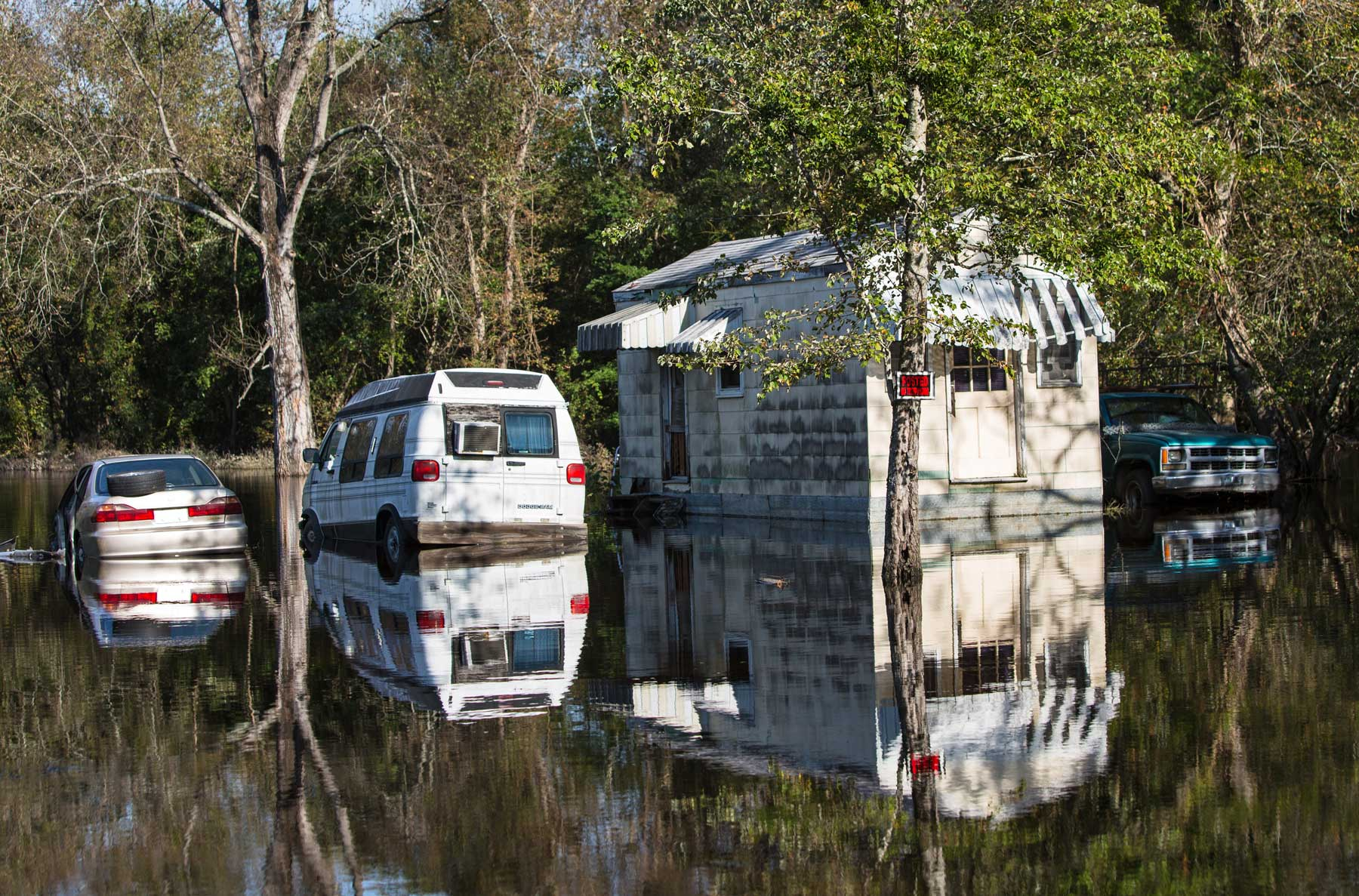 A home and cars are mirrored in the floodwaters of Hurricane Matthew. (Julie Dermansky)