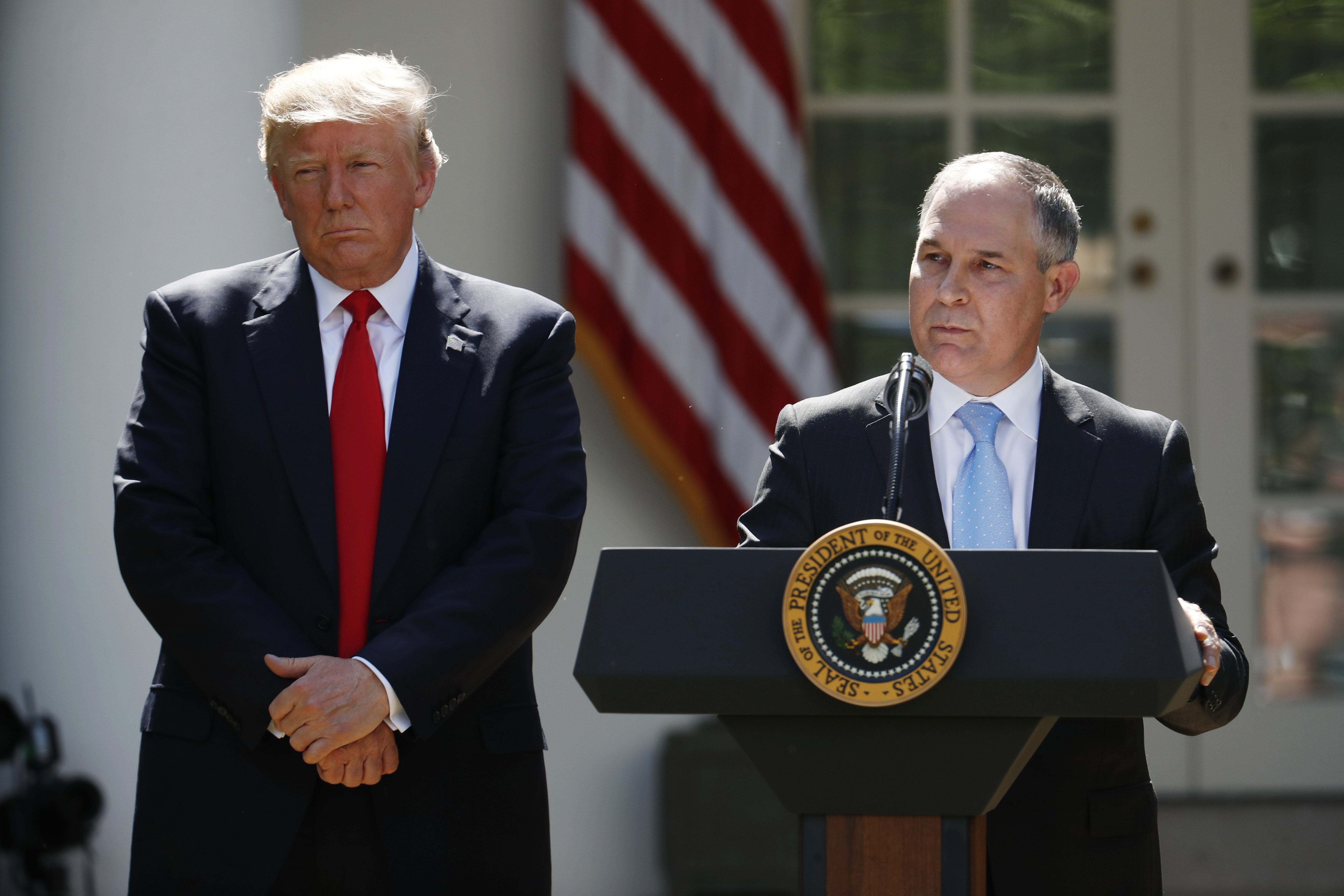 In this June 1, 2017, photo, President Donald Trump listens as EPA Administrator Scott Pruitt speaks about the U.S. role in the Paris climate change accord in the Rose Garden of the White House in Washington. Trump's environmental chief has been trying to clear the air about why his boss is pulling out of the Paris climate accord, but some of the claims he's making are as solid as smoke. (AP Photo/Pablo Martinez Monsivais)