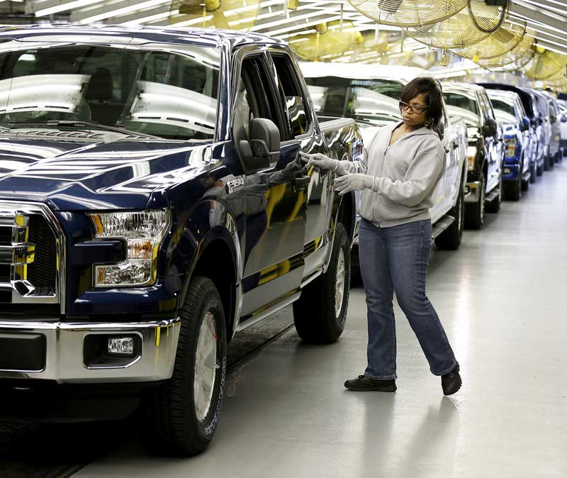 A worker inspects the aluminum-alloy body Ford F-150 truck at the company's Kansas City Assembly Plant, in Claycomo, Missouri. Ford made its best-selling vehicle 700 pounds lighter in 2015 to improve fuel economy. (AP Photo/Charlie Riedel)