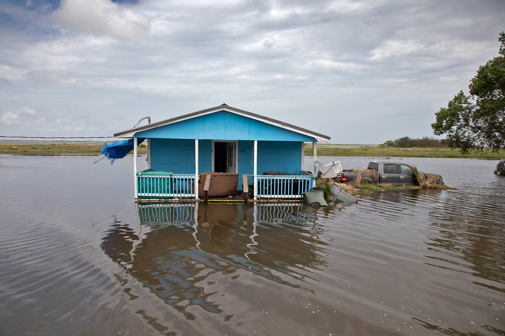 Floodwaters reach the porch of a home on Isle de Jean Charles. The island was not under mandatory evacuation, the surge came as a surprise to residents, though it's a common occurrence during storms.