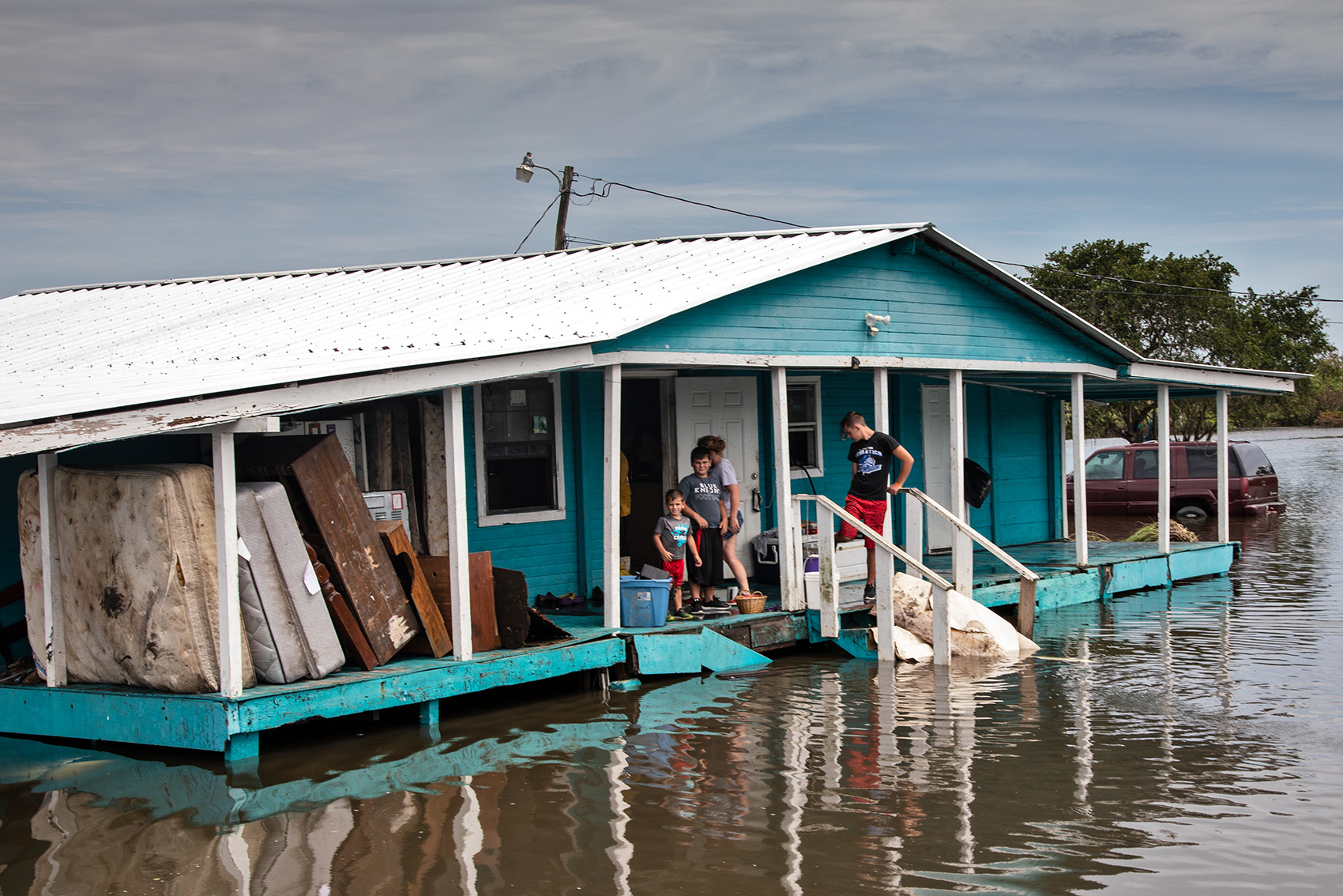 Family members return to a relative's home on Isle de Jean Charles to asses the damage.