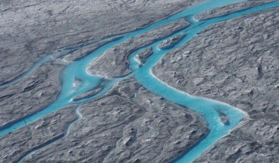 In this image taken on Thursday, August 1, 2019, large rivers of melting water form on an ice sheet in western Greenland and drain into moulin holes that empty into the ocean from underneath the ice. The heat dome that smashed high temperature records in five European countries a week ago moved over Greenland in late July and early August, accelerating the melting of the island's ice sheet and causing massive ice loss in the Arctic. (Caspar Haarløv, Into the Ice via AP)