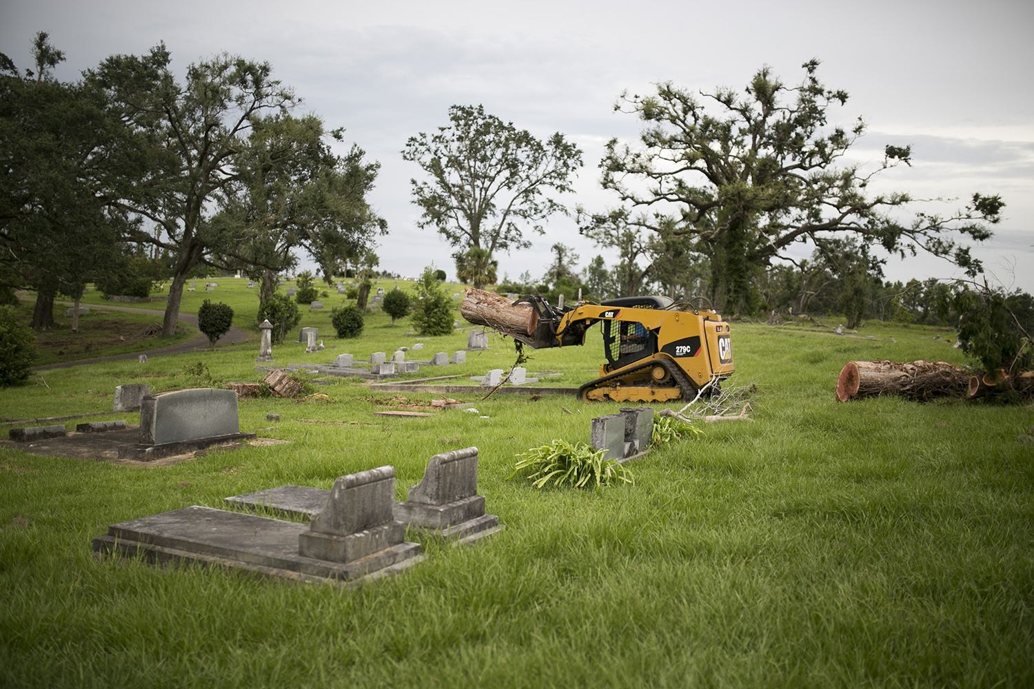 Chris Stallings hauls off felled trees from Riverside Cemetery in Marianna, Fla., nine months after Hurricane Michael. Stallings, who is from Mississippi, is one of the many workers who have temporarily moved to the region to join clean up crews.