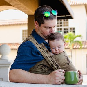 Dad cuddling baby in Wrapsody Dinah wrap with mug of tea or coffee