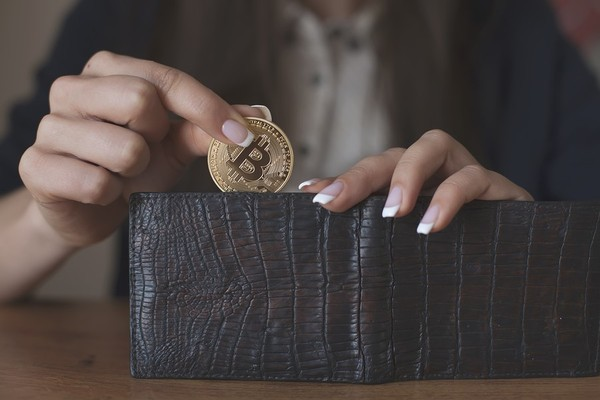 Woman placing bitcoin coins in a wallet.
