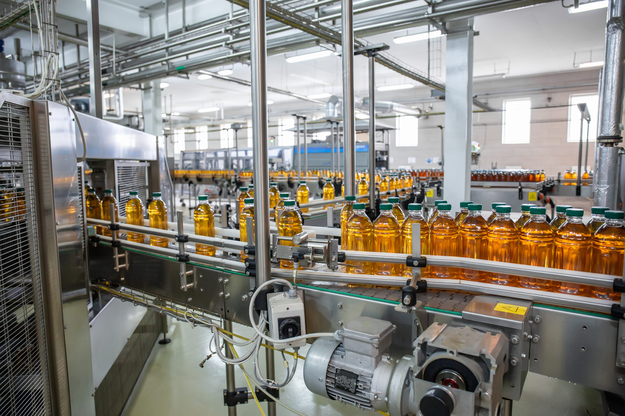 Conveyor belt or line in beverage plant with modern automated industrial machine equipment. Plastic PET bottles with fresh organic juice in factory interior