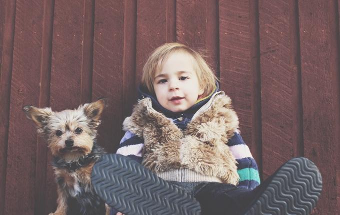 enfant assis contre un mur avec son chien