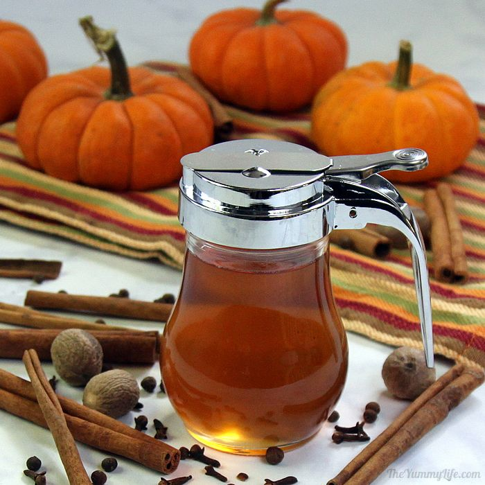 A pitcher of syrup is surrounded by cinnamon sticks, nuts, pumpkins and other spices