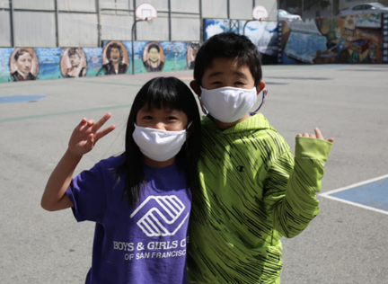 Photo of two young kids wearing masks posing for a photo.