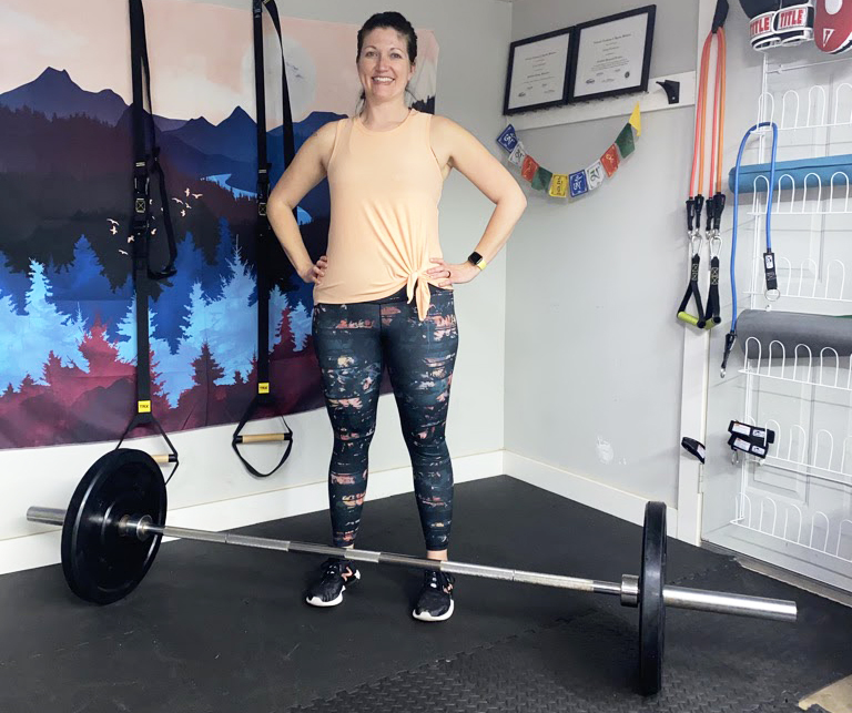 Trainer Jaimie Konsitzke in home gym w/ J-Fit bumper plates, 45-lb Olympic barbell.