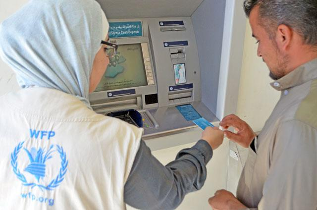 A member of the World Food Programme team assists a Syrian refugee in using the blockchain method in Azraq refugee camp