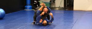 two men practicing jiu jitsu on a mat