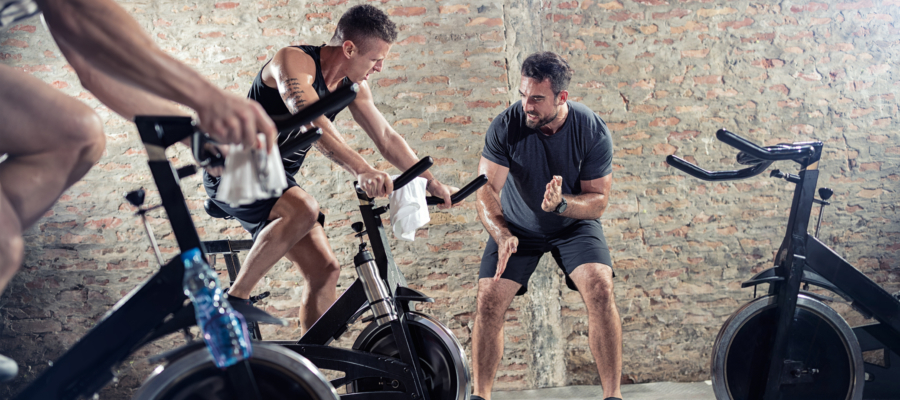 personal trainer encourages student on spinning bike