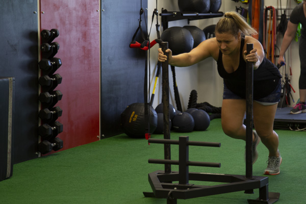 woman pushes weighted sled during training