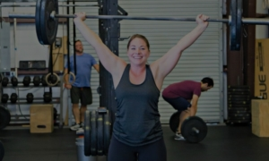 woman lifting heavy weight with men lifting in backgrounbd