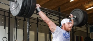 man lifting heavy weight above his head