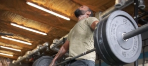 man lifting heavy barbell