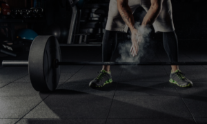 barbell on ground with man standing beside it