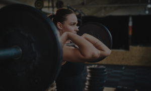 woman lifting a heavy barbell in the gym