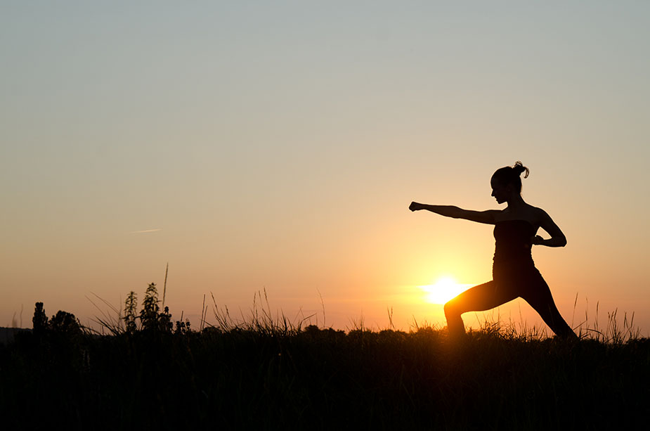 woman fighting with sunset background